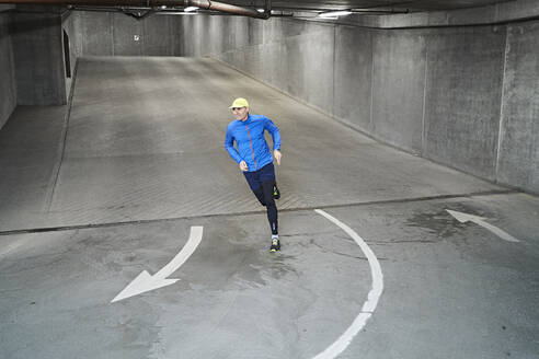 Mature man running in parking garage of residential building - JAHF00084