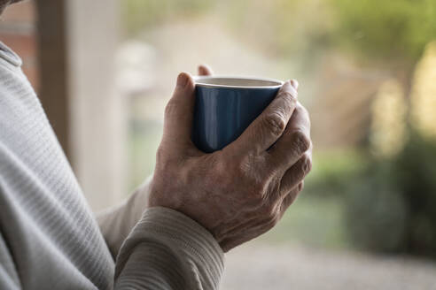 Close-up of man holding coffee cup while standing at home - AFVF07886