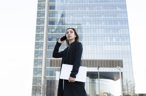 Young businesswoman with laptop talking on mobile phone while standing in city - JCCMF00278