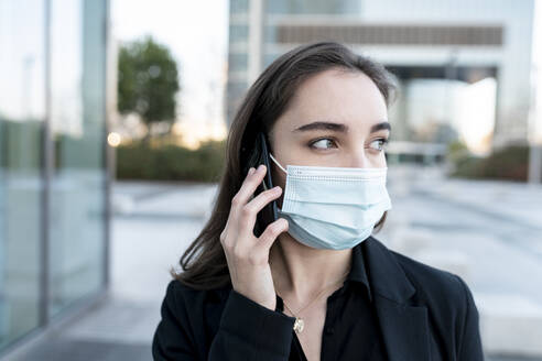 Businesswoman with protective face mask looking away while talking on mobile phone outdoors - JCCMF00287