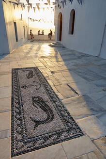 Sunset in Plaka, the main town on Milos, with Greek Orthodox feast decoration on the church square with pebble mosaic, Plaka, Milos, Cyclades, Greek Islands, Greece, Europe - RHPLF18867