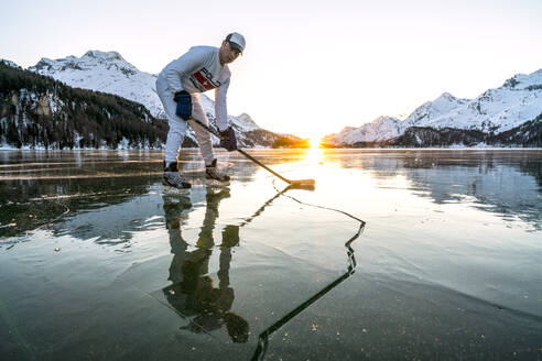 Front view of ice hockey player on cracked surface of frozen Lake Sils, Engadine, Graubunden canton, Switzerland, Europe - RHPLF18951