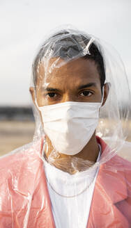 Man wearing raincoat and protective face mask staring while standing outdoors - AFVF07899