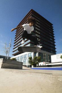 Man practicing kickflip with skateboard while jumping at skateboard park - PNAF00378