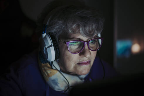 Close-up of senior teacher wearing eyeglasses while working over laptop at home - OIPF00071