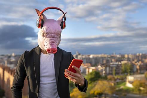 Businessman wearing pig mask and wireless headphones using smart phone against sky - GGGF00576