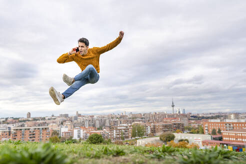 Young man on the phone jumping over hill against cloudy sky - GGGF00579