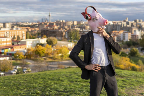 Thoughtful male professional wearing pig mask and wireless headphones against sky - GGGF00588