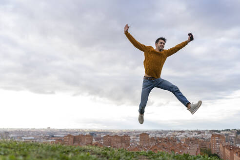 Excited young man holding mobile phone while jumping on hill against cityscape - GGGF00606