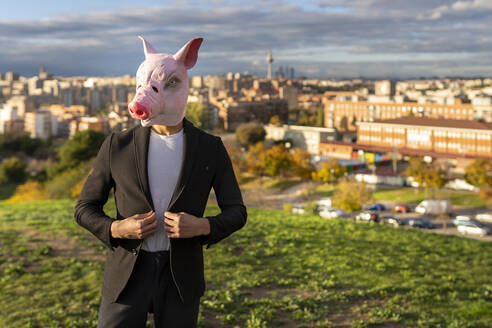 Businessman wearing pig mask while standing on hill against sky - GGGF00618