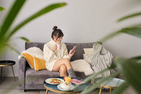 Smiling woman using smart phone while having coffee on sofa at home during winter - AODF00086