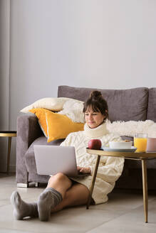 Woman in sweater using laptop while sitting on floor in living room at home - AODF00110