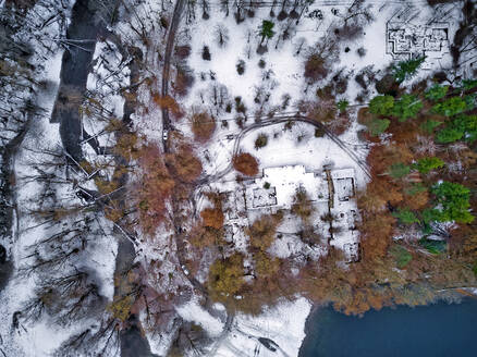 Aerial view of country road stretching through snow-covered landscape - KNTF06047