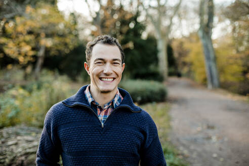 Smiling mid adult man standing in front of trees in public park - KVF00145