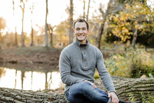 Smiling mid adult man sitting on log in public park - KVF00148