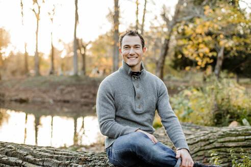 Smiling mid adult man sitting on log in public park - KVF00148