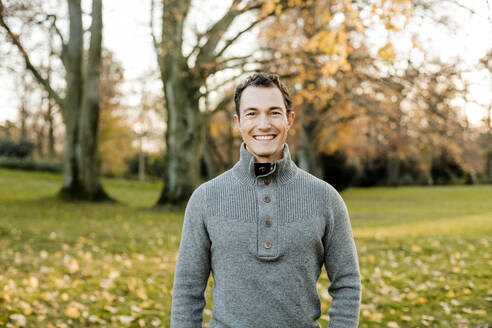 Cheerful handsome man standing in front of trees in public park during autumn - KVF00151