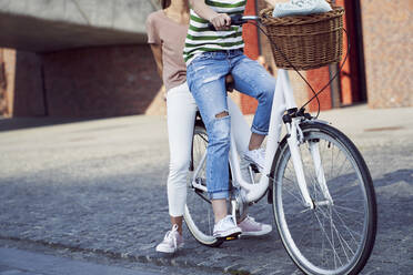 Female friends traveling on bicycle in city during weekend - ABIF01284