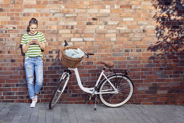 Woman text messaging through mobile phone while bicycle parked on footpath against brick wall - ABIF01290