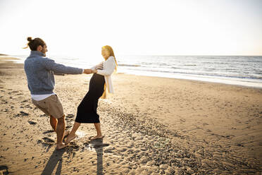 Cheerful couple holding hands while dancing at beach against clear sky during sunny day - UUF22353
