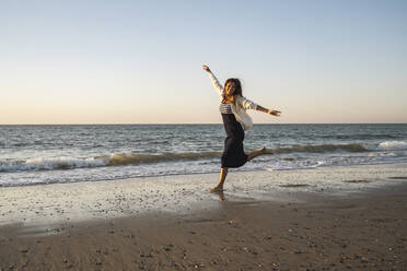 Carefree woman running at beach against clear sky during sunset - UUF22359