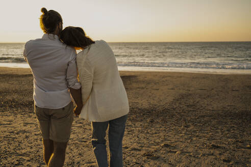 Romantic couple walking at beach during sunset - UUF22371
