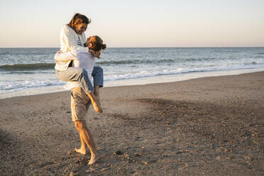 Carefree young man lifting girlfriend at beach during sunset - UUF22374