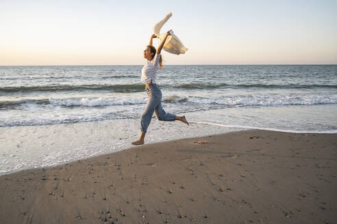 Carefree woman running at beach against clear sky during sunset - UUF22377