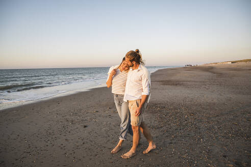 Romantic young couple walking at beach against clear sky during vacation - UUF22383