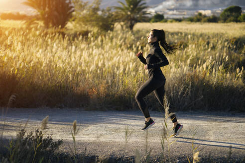 Young woman running on footpath against green landscape at sunset - MPPF01351