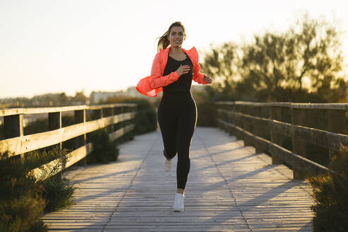 Smiling young woman running on footbridge against clear sky during sunset - MPPF01363