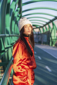 Woman wearing knit hat and tracksuit standing with hands in pockets on bridge - JRVF00051