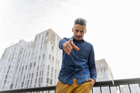 Confident man pointing while standing against sky - AFVF07969