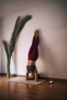 Young woman practicing headstand on mat by wall at home - GRCF00589
