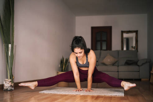 Young woman with legs apart balancing on mat at home - GRCF00592