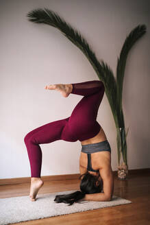 Woman practicing headstand on mat by wall at home - GRCF00595