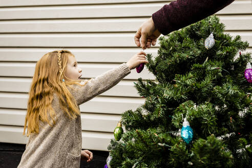 Hand of father assisting daughter in decorating Christmas tree in yard - AWAF00011