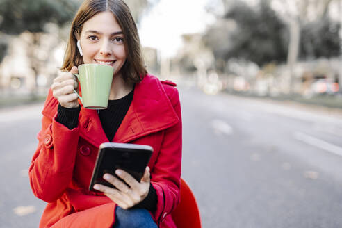 Fashionable young woman having coffee while holding digital tablet on street - JCZF00364
