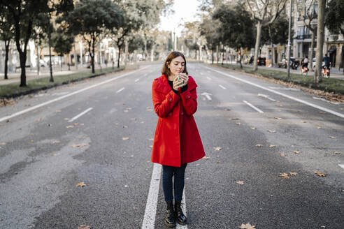 Fashionable woman wearing red jacket holding coffee cup with eyes closed on street - JCZF00391