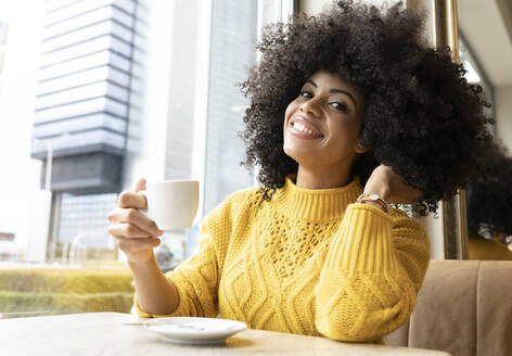 Young woman with hand in hair holding coffee cup while sitting at cafe - JCCMF00358
