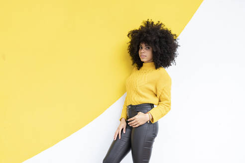 Curly hair woman with hands in pockets leaning on wall - JCCMF00376