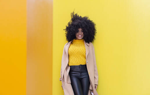 Smiling curly hair woman leaning on yellow wall - JCCMF00412
