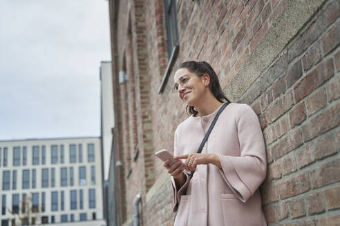 Smiling businesswoman looking away holding smart phone while leaning on brick wall - SDAHF01049