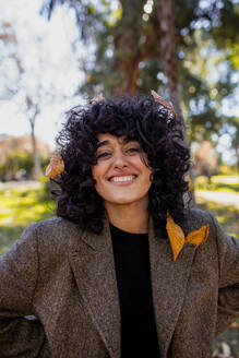 Curly hair woman smiling while standing at park - MRRF00756