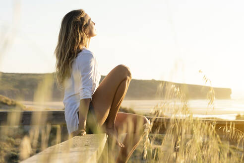 Woman resting while sitting on railing at beach - SBOF02320