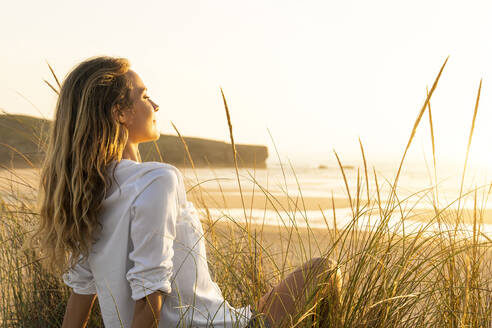 Woman looking at view while sitting on grass at beach - SBOF02326