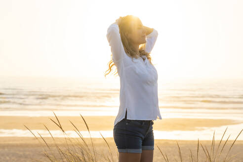 Carefree woman with hands behind head standing at beach - SBOF02329