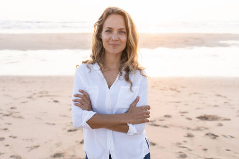 Smiling woman standing with arms crossed at beach - SBOF02347