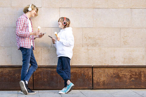 Friends wearing headphones smiling while standing with mobile phone and ice cream against wall - GGGF00672
