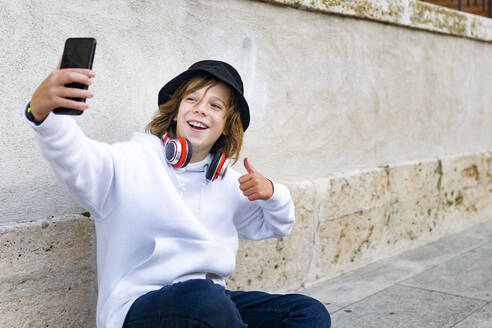 Boy wearing hat and headphones using mobile phone while sitting against wall - GGGF00684